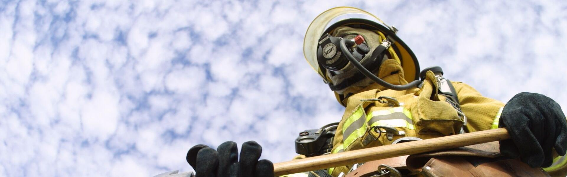 fire fighter viewed from below with sky and clouds